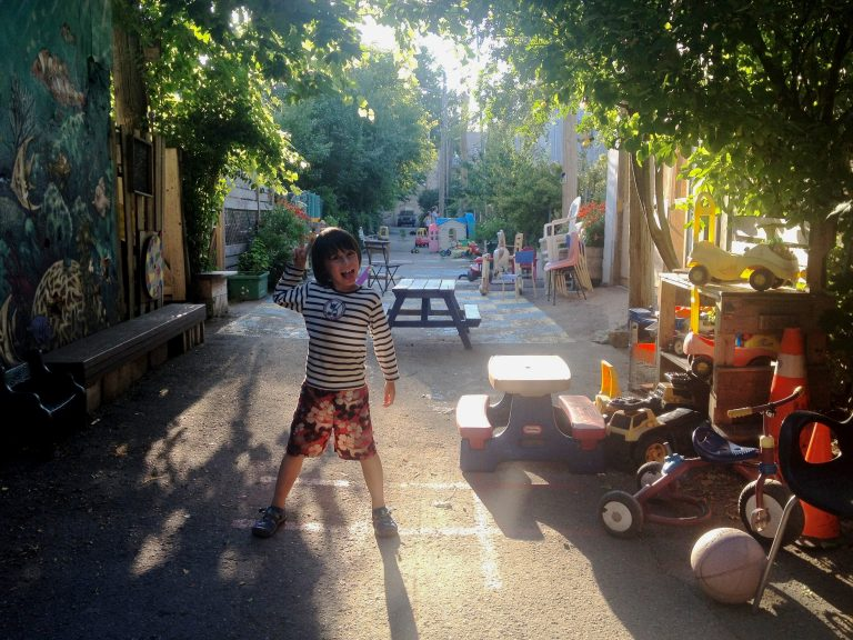 A boy poses while playing in a green alley