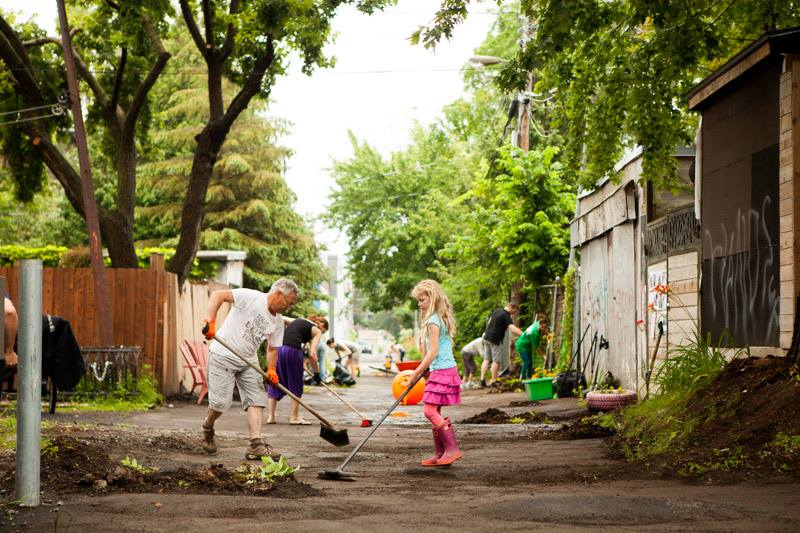 A man and a girl sweep the ground of an alley, other people work in the background