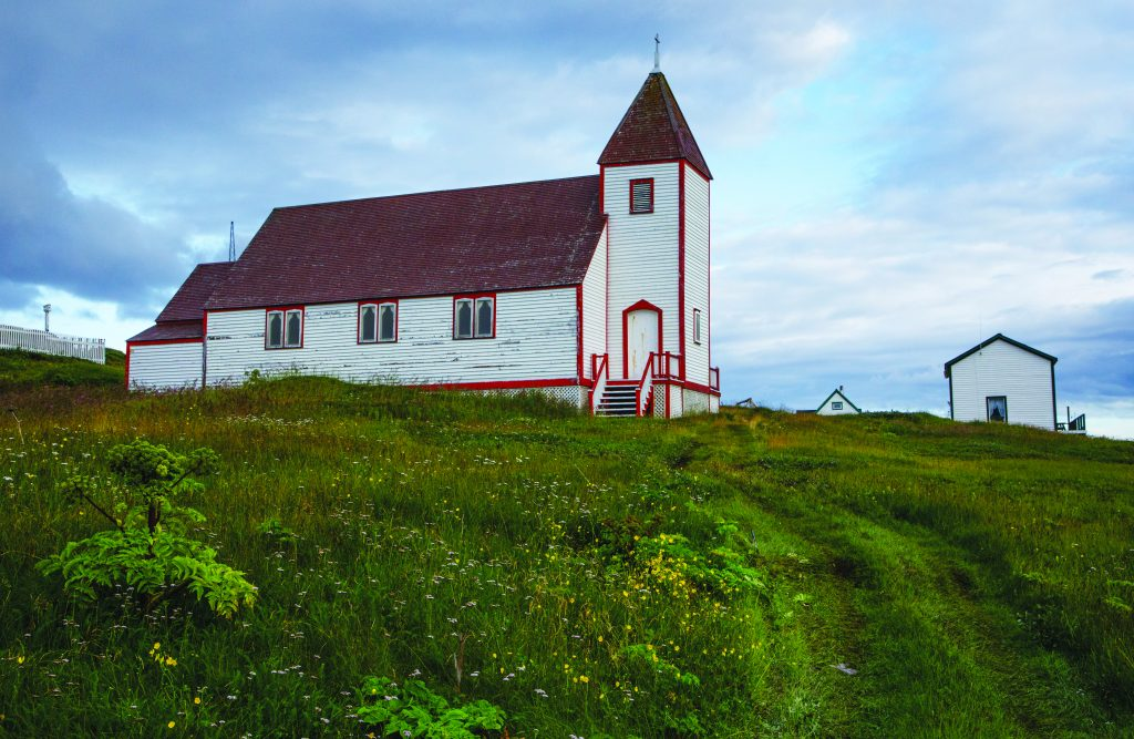 St James Anglican church stands tall and white on top of a grassy slope.