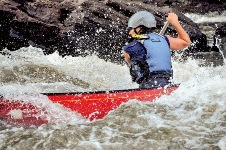 A whitewater rafter paddles down a river in quebec