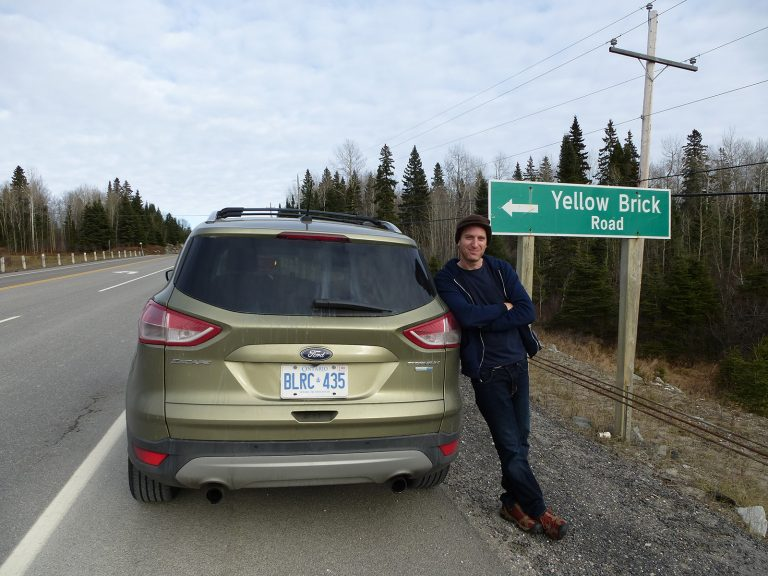 A man stands next to a car and beneath a sign for Yellow Brick Road